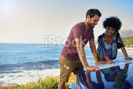 istock Young lovely couple using map during roadtrip 846518712