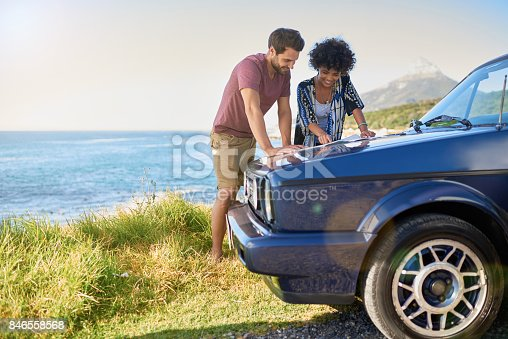istock Young lovely couple using map during roadtrip 846558568
