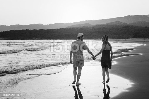 young lovely couple walking on windy coast line. Back horizontal view.