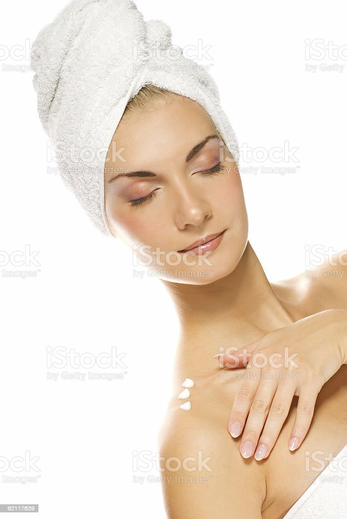 Young lovely lady applying moisturizer to her skin after shower royalty-free stock photo