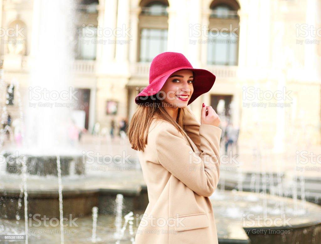 通り観光の町にコートと紫の帽子で、若い素敵な女性 ストックフォト
