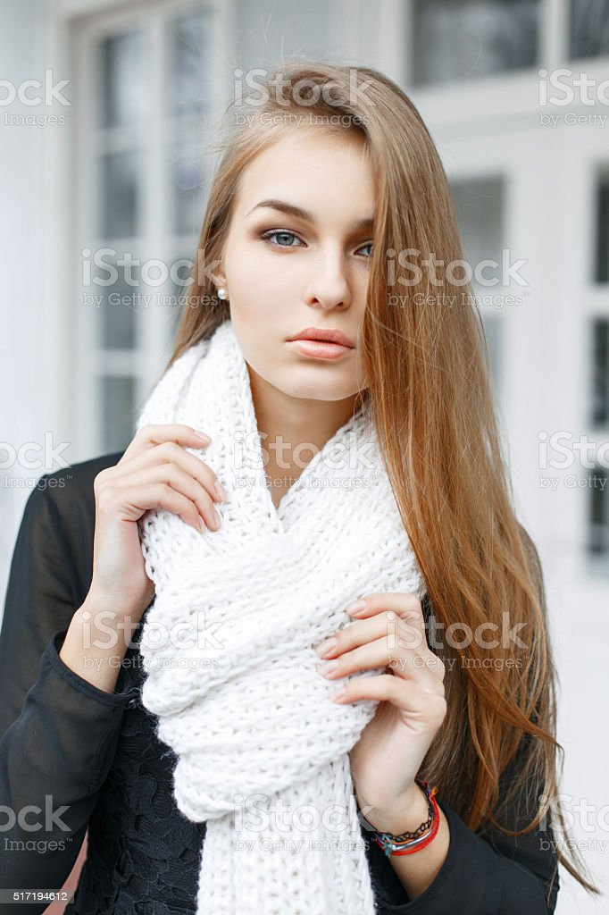 Young lovely woman with a white knitted scarf stock photo