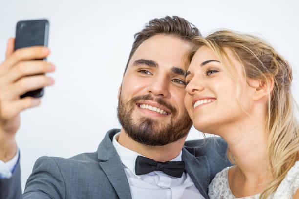 junge geliebte ehepaar in hochzeitskleid tun selfie und video-anruf zusammen - hochzeitskleider online stock-fotos und bilder
