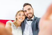 Married couple in wedding dress doing selfie together and sit on sofa