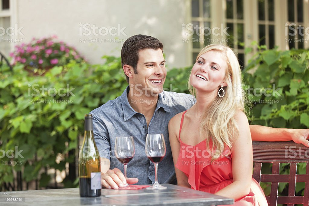 Young Lovers Enjoying Glass of Wine in Outdoor Restaurant Hz royalty-free stock photo
