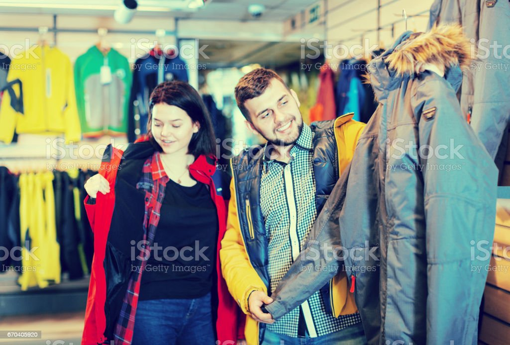 Young loving couple buying windcheater in store stock photo