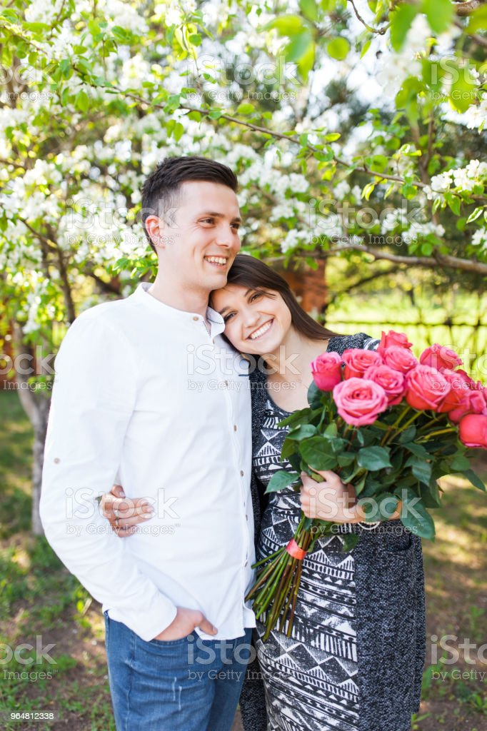 young loving couple in love, girl holding flowers, happy and enjoy the beautiful nature, advertising, and utsava text royalty-free stock photo