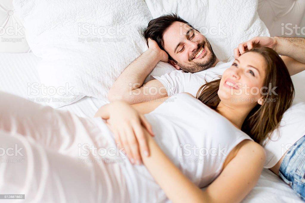 Pareja joven amante en la cama - foto de stock