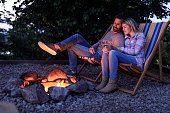 Loving couple relaxing in deck chairs by the campfire at their backyard in the evening.