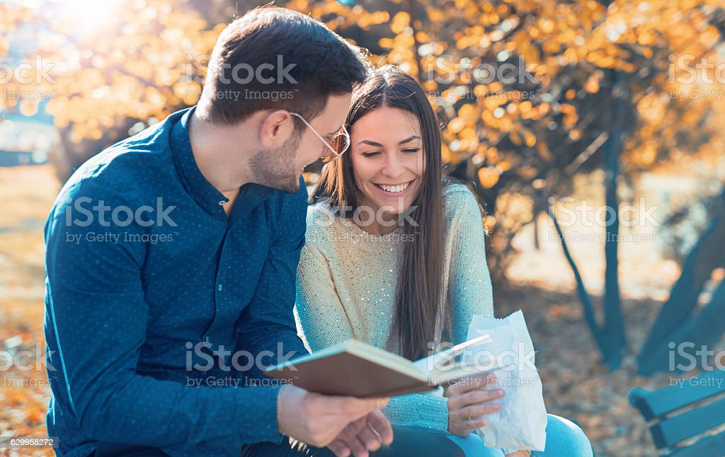 Young loving couple sitting on the bench in autumn park stock photo