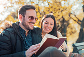 istock Young loving couple sitting on the bench in the autumn 636688296