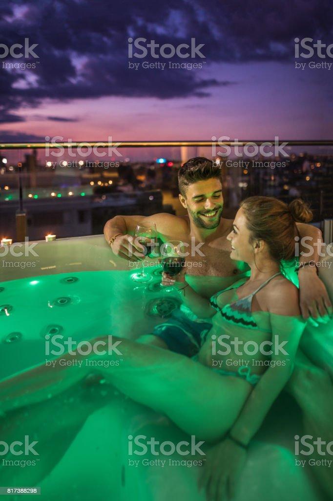 Jeune loving couple grillage avec du vin dans un bain à remous. - Photo