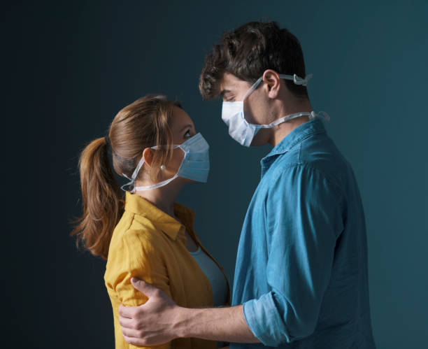 Young loving couple wearing face masks stock photo