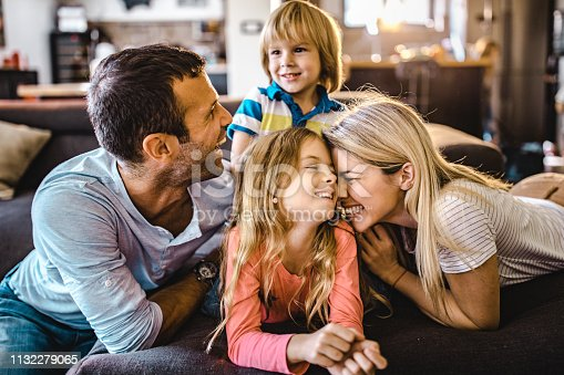 1159543952istockphoto Young loving family having fun together in the living room. 1132279065