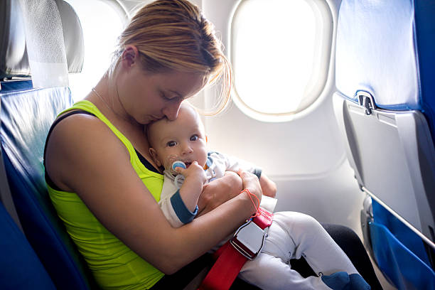 Young loving mother and her baby traveling by airplane. stock photo