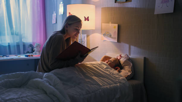 Young Loving Mother Reads Bedtime Stories to Her Little Beautiful Daughter who Goes to Sleep in Her Bed. Young Loving Mother Reads Bedtime Stories to Her Little Beautiful Daughter who Goes to Sleep in Her Bed. ultra high definition television stock pictures, royalty-free photos & images