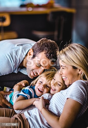 1159543952istockphoto Young loving parents enjoying with their small kids at home. 1132278961