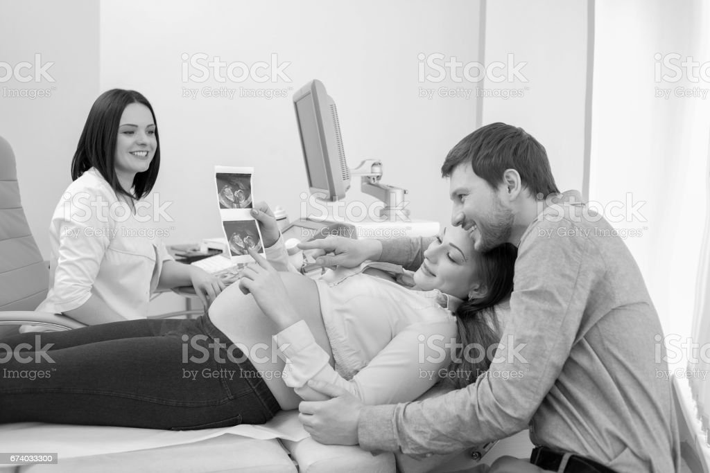 Young loving pregnant couple visiting doctor together monochrome stock photo