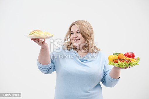 1132777983 istock photo Young lush fat woman in casual blue clothes on a white background holding a vegetable salad and a plate of fast food, hamburger and fries. Diet and proper nutrition. 1132778093