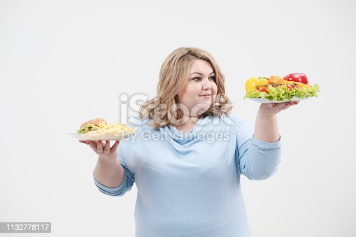 1132777983 istock photo Young lush fat woman in casual blue clothes on a white background holding a vegetable salad and a plate of fast food, hamburger and fries. Diet and proper nutrition. 1132778117
