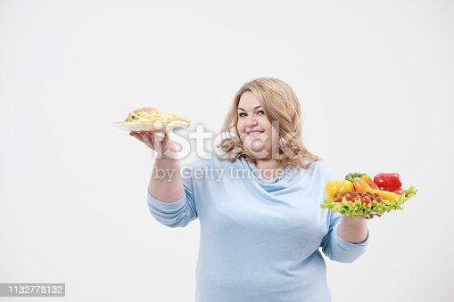 1132777983 istock photo Young lush fat woman in casual blue clothes on a white background holding a vegetable salad and a plate of fast food, hamburger and fries. Diet and proper nutrition. 1132778132