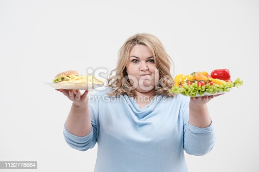 1132777983 istock photo Young lush fat woman in casual blue clothes on a white background holding a vegetable salad and a plate of fast food, hamburger and fries. Diet and proper nutrition. 1132778664