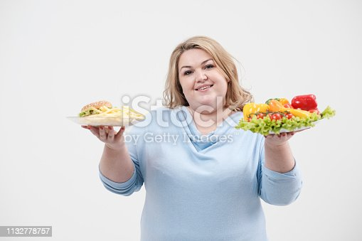 1132777983 istock photo Young lush fat woman in casual blue clothes on a white background holding a vegetable salad and a plate of fast food, hamburger and fries. Diet and proper nutrition. 1132778757