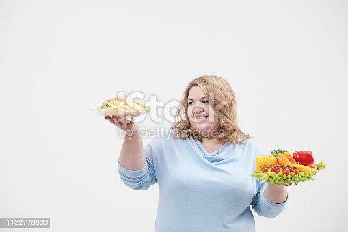 1132777983 istock photo Young lush fat woman in casual blue clothes on a white background holding a vegetable salad and a plate of fast food, hamburger and fries. Diet and proper nutrition. 1132778833