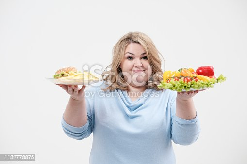 1132777983 istock photo Young lush fat woman in casual blue clothes on a white background holding a vegetable salad and a plate of fast food, hamburger and fries. Diet and proper nutrition. 1132778875