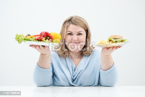 1132777983 istock photo Young lush fat woman in casual blue clothes on a white background holding a vegetable salad and a plate of fast food, hamburger and fries. Diet and proper nutrition. 1132788636