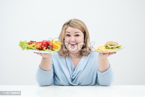 1132777983 istock photo Young lush fat woman in casual blue clothes on a white background holding a vegetable salad and a plate of fast food, hamburger and fries. Diet and proper nutrition. 1132788659