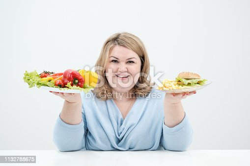 1132777983 istock photo Young lush fat woman in casual blue clothes on a white background holding a vegetable salad and a plate of fast food, hamburger and fries. Diet and proper nutrition. 1132788675