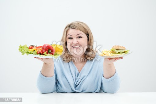 1132777983 istock photo Young lush fat woman in casual blue clothes on a white background holding a vegetable salad and a plate of fast food, hamburger and fries. Diet and proper nutrition. 1132788684