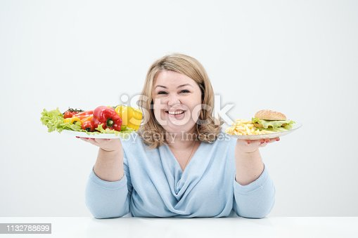 1132777983 istock photo Young lush fat woman in casual blue clothes on a white background holding a vegetable salad and a plate of fast food, hamburger and fries. Diet and proper nutrition. 1132788699