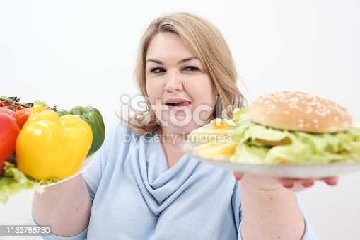 1132777983 istock photo Young lush fat woman in casual blue clothes on a white background holding a vegetable salad and a plate of fast food, hamburger and fries. Diet and proper nutrition. 1132788730