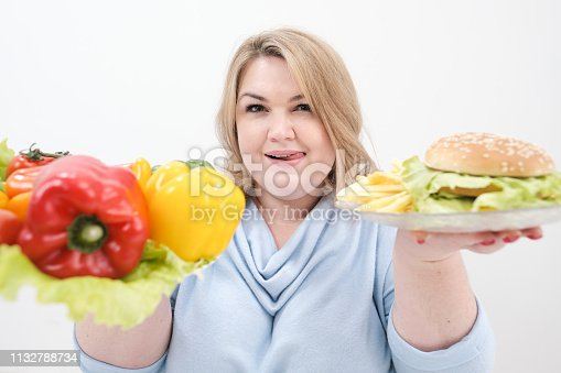 1132777983 istock photo Young lush fat woman in casual blue clothes on a white background holding a vegetable salad and a plate of fast food, hamburger and fries. Diet and proper nutrition. 1132788734