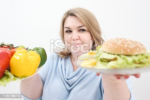1132777983 istock photo Young lush fat woman in casual blue clothes on a white background holding a vegetable salad and a plate of fast food, hamburger and fries. Diet and proper nutrition. 1132788742