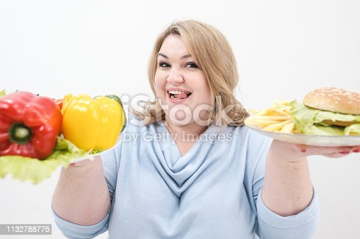 1132777983 istock photo Young lush fat woman in casual blue clothes on a white background holding a vegetable salad and a plate of fast food, hamburger and fries. Diet and proper nutrition. 1132788775