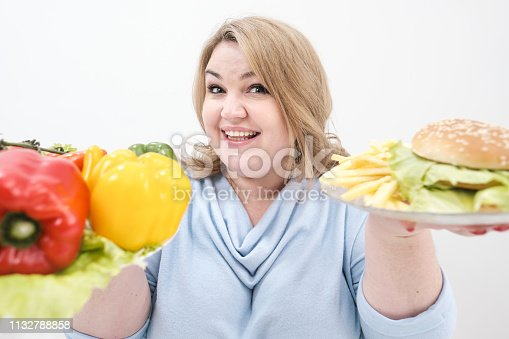 1132777983 istock photo Young lush fat woman in casual blue clothes on a white background holding a vegetable salad and a plate of fast food, hamburger and fries. Diet and proper nutrition. 1132788858