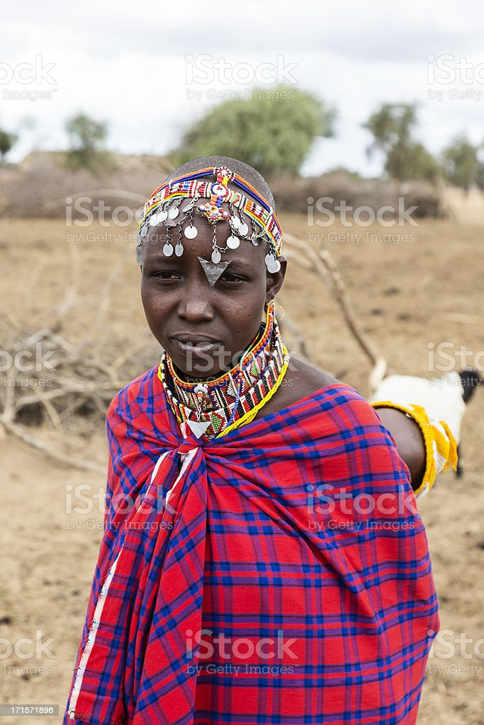 Young Maasai mother with child on back outide village. stock photo