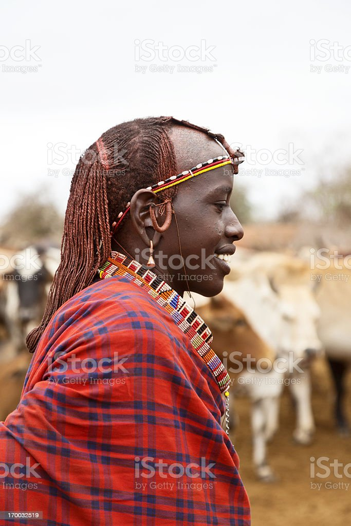Young Maasai warrior (moran) with cattle in background, royalty-free stock photo