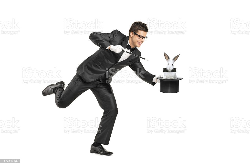 Young magician holding a top hand with rabbit in it stock photo