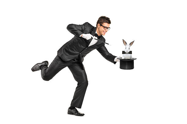 Young magician holding a top hand with rabbit in it Full length portrait of a magician holding a top hat with a rabbit on it isolated on white background magician stock pictures, royalty-free photos & images