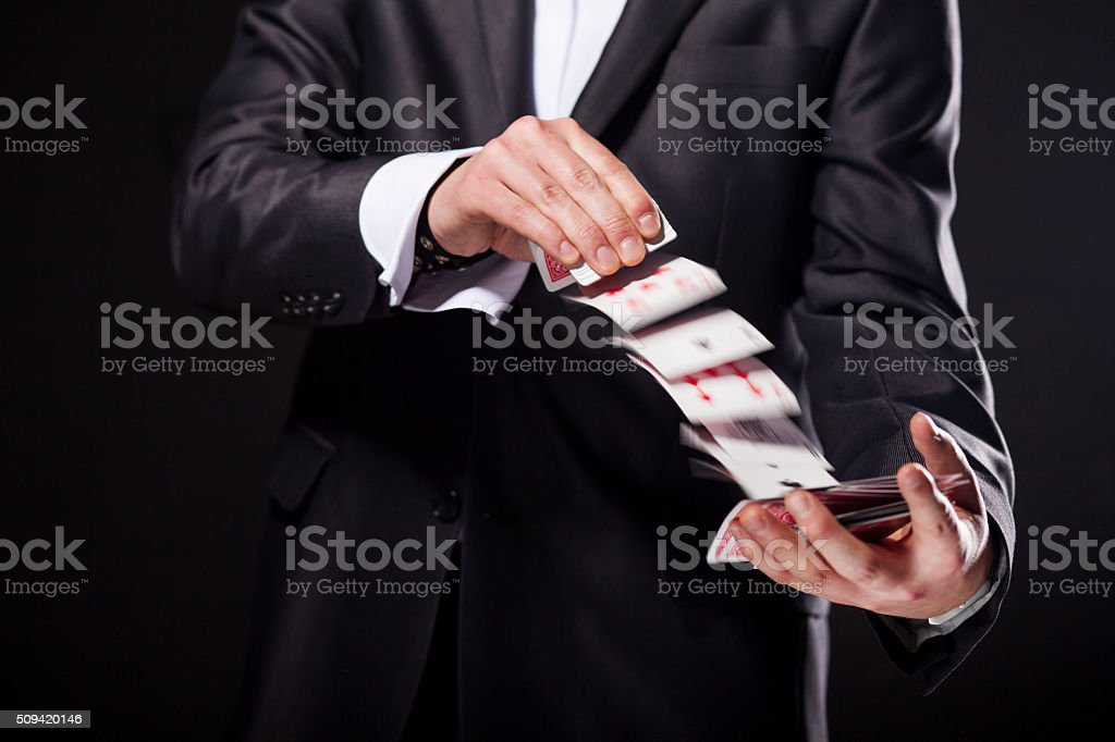 Young magician showing tricks using cards from deck. Close up. stock photo