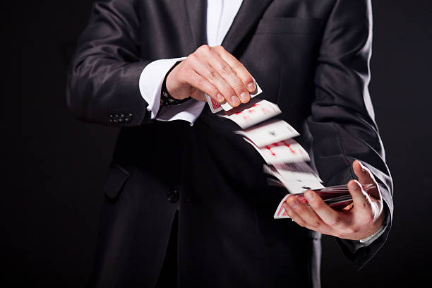 young magician showing tricks using cards from deck. close up. - magician stock photos and pictures