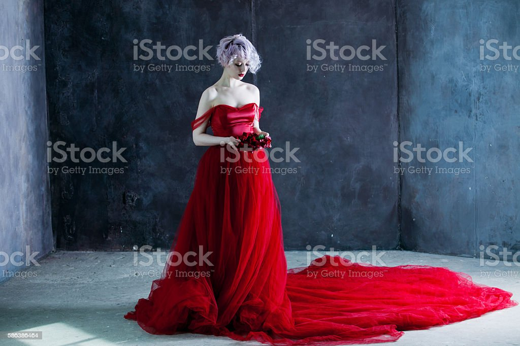 young magnificent woman in red dress holds a wreath of stock photo