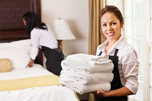 young maids cleaning and preparing room for hotel guests - maid stock pictures, royalty-free photos & images