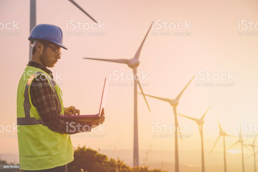 Young maintanence engineer using computer in wind turbine farm at sunset stock photo