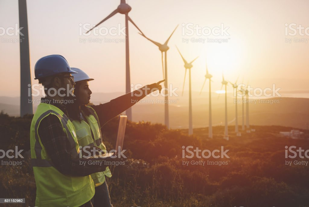 Young maintenance engineer team working in wind turbine farm at sunset Young electrical engineer woman and business man standing in front of wind turbines checking and working about technical problems and writes the results of measurements with laptop pc in wind power plant electric energy station. xxxl size taken with canon 5d mIV 20-29 Years Stock Photo