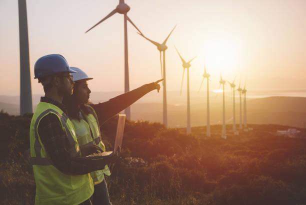 equipo de mantenimiento joven ingeniero trabajando en granja de turbinas de viento al atardecer - ingeniero fotografías e imágenes de stock